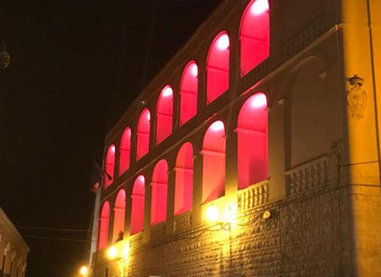 La facciata del Palazzo di Città colorata di rosso Adisco